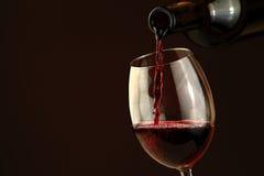 Vino rojo que vierte en un vidrio de vino Imagen de archivo