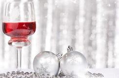 Vino rojo y bolas de la Navidad contra y luces del día de fiesta Imagenes de archivo