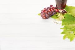 Vino rojo y uvas con las hojas en el fondo de madera blanco, un horizontal con el sitio o el espacio para sus palabras, texto o co Imagenes de archivo
