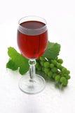 Vino rojo y uvas en la hoja imagen de archivo