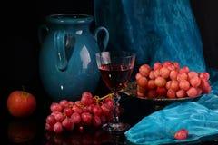 Vino rojo y uvas rosadas en un fondo negro Foto de archivo libre de regalías