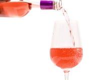 Vino rosado que vierte en el vidrio Imágenes de archivo libres de regalías