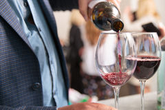 Vino rosso che è versato dentro il vetro Immagini Stock