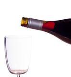 Vino rosso che è versato nel vetro Immagini Stock Libere da Diritti