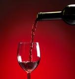 Vino rosso che è versato nel vetro di vino Immagini Stock Libere da Diritti