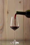 Vino rosso che è versato in una bottiglia di vetro di vino rosso con un vetro brillante su un fondo di legno su un supporto di ve Immagini Stock Libere da Diritti