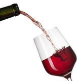 Vino rosso che versa nel vetro con spruzzata isolata su bianco Immagini Stock