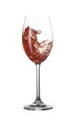 Vino rosso che versa nel vetro con spruzzata isolata su bianco Immagini Stock Libere da Diritti