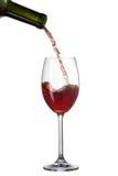 Vino rosso che versa nel vetro con spruzzata isolata su bianco Fotografia Stock Libera da Diritti