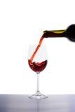 Vino rosso che versa nel vetro di vino Fotografie Stock Libere da Diritti