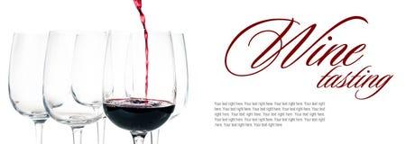 Vino rosso che versa nel vetro vuoto Fotografie Stock