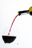 Vino rosso che versa in un vetro Fotografie Stock Libere da Diritti