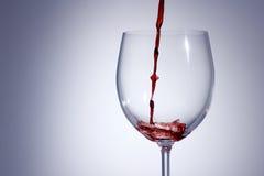 Vino rosso che versa in un vetro con la a con fondo Immagine Stock Libera da Diritti