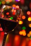 Vino rosso con gli indicatori luminosi di natale Fotografie Stock Libere da Diritti