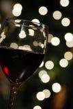 Vino rosso con gli indicatori luminosi di natale Immagini Stock Libere da Diritti
