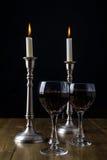 Vino rosso con le candele sulla tavola di legno fotografia stock
