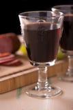 Vino rosso con salame e l'uva sulla vecchia tavola di legno e su una certa uva immagini stock
