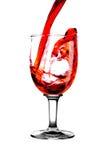 Vino rosso del flusso in vetro Immagini Stock