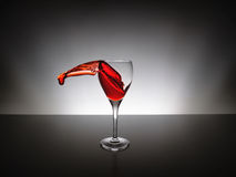Vino rosso della spruzzata su vetro Fotografie Stock Libere da Diritti