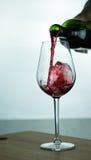 Vino rosso di caduta in vetro Fotografie Stock Libere da Diritti
