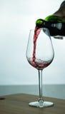 Vino rosso di caduta in vetro Fotografie Stock