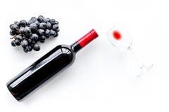 Vino rosso di gusto Bottiglia dell'uva di vetro e nera del vino rosso, sul copyspace bianco di vista superiore del fondo fotografie stock libere da diritti
