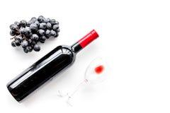Vino rosso di gusto Bottiglia dell'uva di vetro e nera del vino rosso, sul copyspace bianco di vista superiore del fondo immagini stock