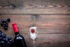 Vino rosso di gusto Bottiglia dell'uva di vetro e nera del vino rosso, sul copyspace di legno scuro di vista superiore del fondo immagine stock libera da diritti