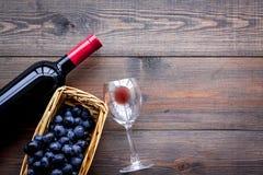 Vino rosso di gusto Bottiglia dell'uva di vetro e nera del vino rosso, sul copyspace di legno scuro di vista superiore del fondo fotografie stock libere da diritti