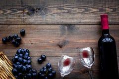 Vino rosso di gusto Bottiglia dell'uva di vetro e nera del vino rosso, sul copyspace di legno scuro di vista superiore del fondo fotografia stock libera da diritti