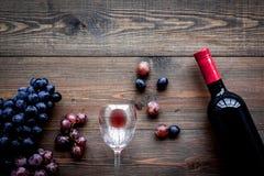 Vino rosso di gusto Bottiglia dell'uva di vetro e nera del vino rosso, sul copyspace di legno scuro di vista superiore del fondo immagini stock libere da diritti