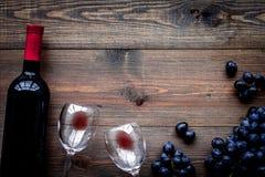 Vino rosso di gusto Bottiglia dell'uva di vetro e nera del vino rosso, sul copyspace di legno scuro di vista superiore del fondo immagini stock