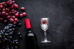 Vino rosso di gusto Bottiglia dell'uva di vetro e nera del vino rosso, sul copyspace di pietra nero di vista superiore del fondo fotografie stock