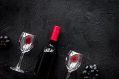 Vino rosso di gusto Bottiglia dell'uva di vetro e nera del vino rosso, sul copyspace di pietra nero di vista superiore del fondo fotografia stock