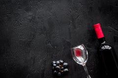 Vino rosso di gusto Bottiglia dell'uva di vetro e nera del vino rosso, sul copyspace di pietra nero di vista superiore del fondo immagini stock
