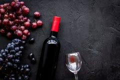 Vino rosso di gusto Bottiglia dell'uva di vetro e nera del vino rosso, sul copyspace di pietra nero di vista superiore del fondo fotografia stock libera da diritti