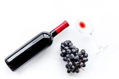 Vino rosso di gusto Bottiglia dell'uva di vetro e nera del vino rosso, sulla vista superiore del fondo bianco fotografia stock