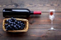 Vino rosso di gusto Bottiglia dell'uva di vetro e nera del vino rosso, sulla vista superiore del fondo di legno scuro immagine stock