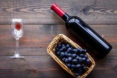 Vino rosso di gusto Bottiglia dell'uva di vetro e nera del vino rosso, sulla vista superiore del fondo di legno scuro fotografia stock