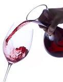 Vino rosso di versamento da un decantatore immagini stock