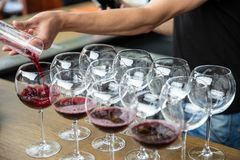 Vino rosso di versamento dal decantatore nel bicchiere di vino sulla fila dei vetri Chiuda su di vino rosso per assistere la cant immagine stock