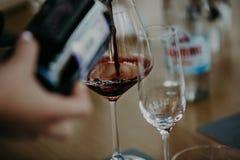 Vino rosso di versamento dalla bottiglia nel bicchiere di vino Immagini Stock Libere da Diritti