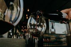 Vino rosso di versamento dalla bottiglia nel bicchiere di vino Fotografia Stock Libera da Diritti