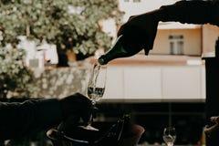 Vino rosso di versamento dalla bottiglia nel bicchiere di vino Fotografia Stock