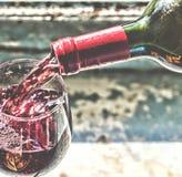 Vino rosso di versamento del vino in un vetro Immagini Stock