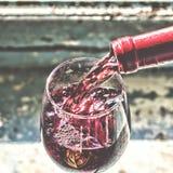 Vino rosso di versamento del vino in un vetro Immagine Stock Libera da Diritti