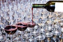 Vino rosso di versamento in molto vetro Fotografie Stock Libere da Diritti
