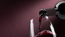 Vino rosso di versamento in un bicchiere di vino Fotografia Stock Libera da Diritti
