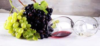 Vino rosso e vino bianco con l'uva ed i vetri su backgr rustico Fotografia Stock