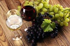 Vino rosso e vino bianco con l'uva ed i vetri su backgr rustico Immagini Stock Libere da Diritti